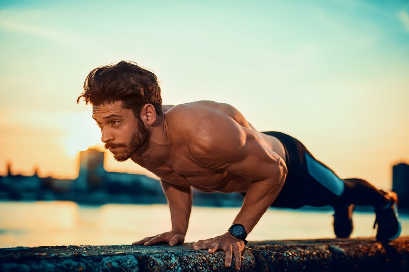 Man doing push ups outside sunrise Shutterstock Strong Fit Well