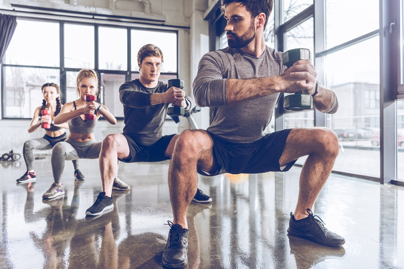 Group training Squats DB Shutterstock Strong Fit Well