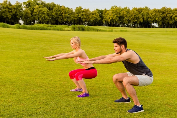 Air squat woman man outdoors Shutterstock Strong Fit Well