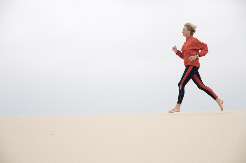 woman running on sand dune shutterstock strong fit well