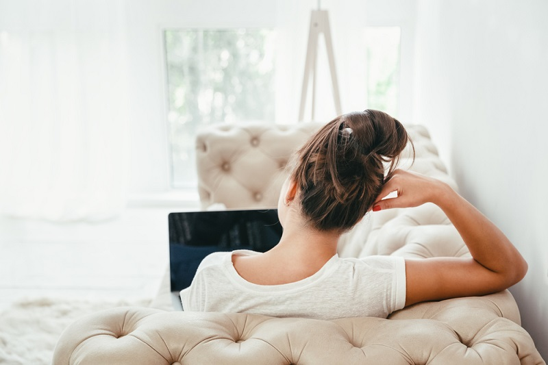 Woman lying on couch with device Shutterstock Strong Fit Well